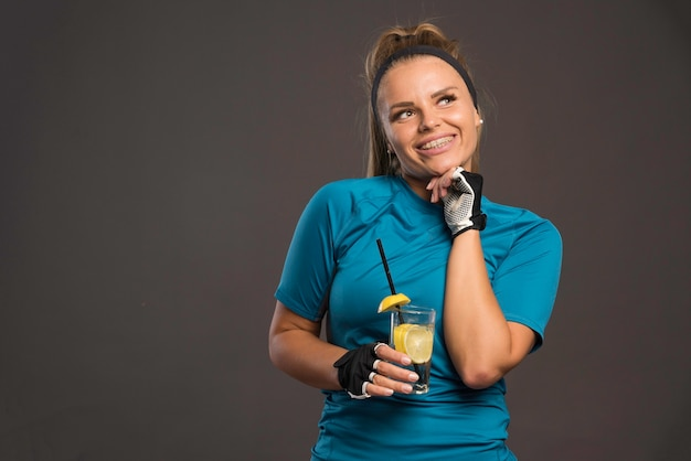 若いスポーティーな女性は、トレーニングとレモンと一緒に水を飲んだ後、幸せです。