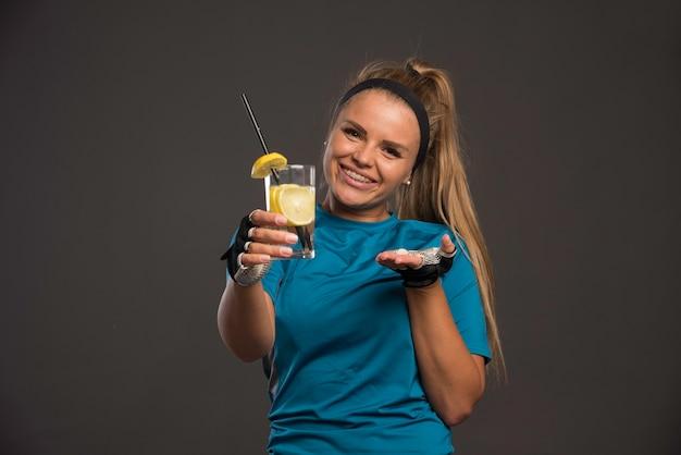 Молодая спортивная женщина, предлагающая воду с лимоном.