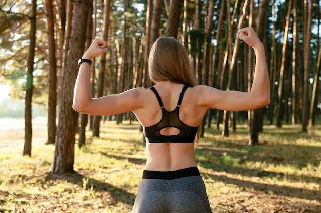 Young sportive woman showing her biceps outdoors, in the park, wearing blac tank top