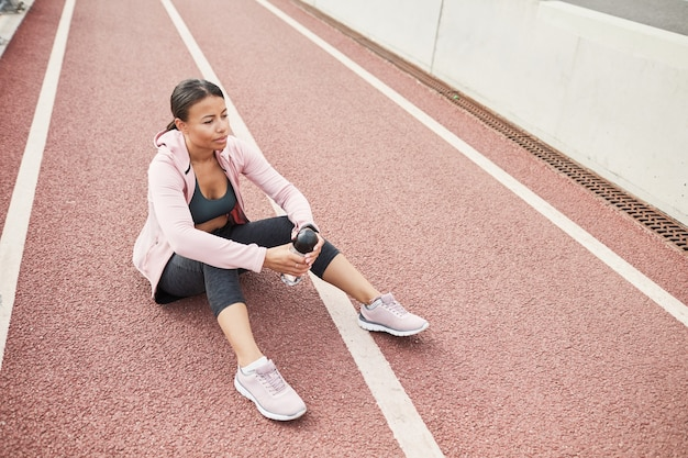 Young sportive woman sitting on the ground with bottle of water and resting after sports training outdoors
