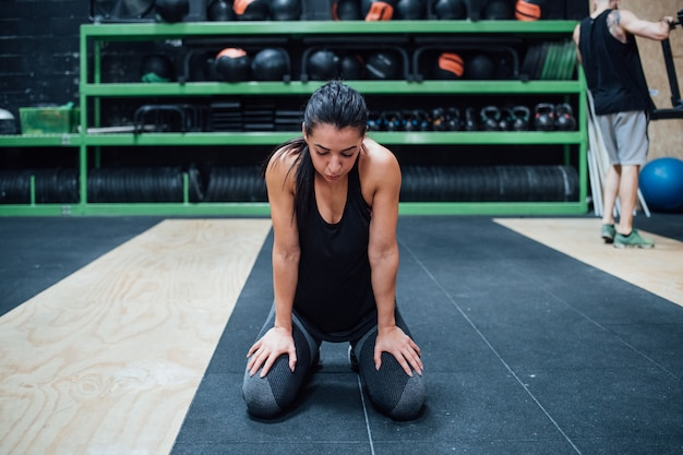 Young sportive woman sitting gym floor taking a break