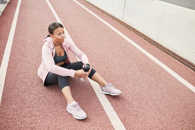 水のボトルで地面に座って、屋外でスポーツトレーニングの後に休んでいる若いスポーツ女性