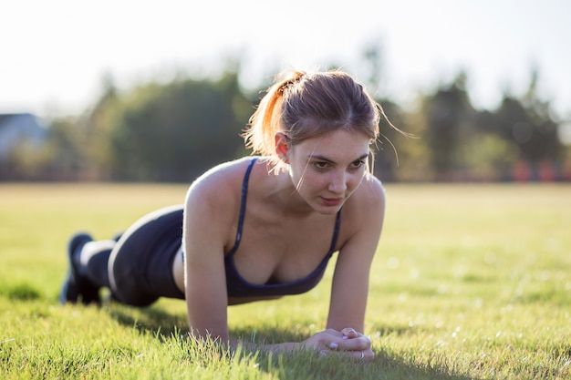 Young sportive woman in sports clothes training in field at sunrise. girl standing in plank position on grass in a park.