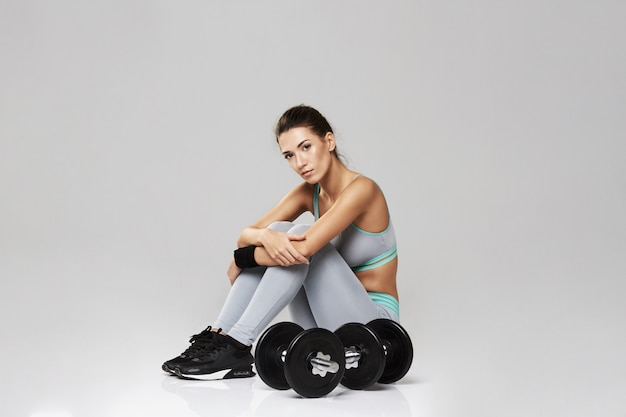 Young sportive woman in sportswear sitting with dumbbells on white.