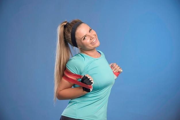 Молодая спортивная женщина протягивает плечи и выглядит позитивно.