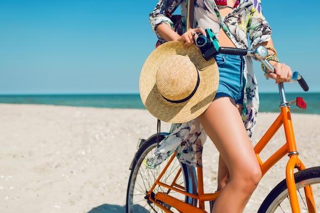 Giovane donna sportiva in elegante top corto bianco e shorts in denim in piedi sulla spiaggia con bicicletta arancione