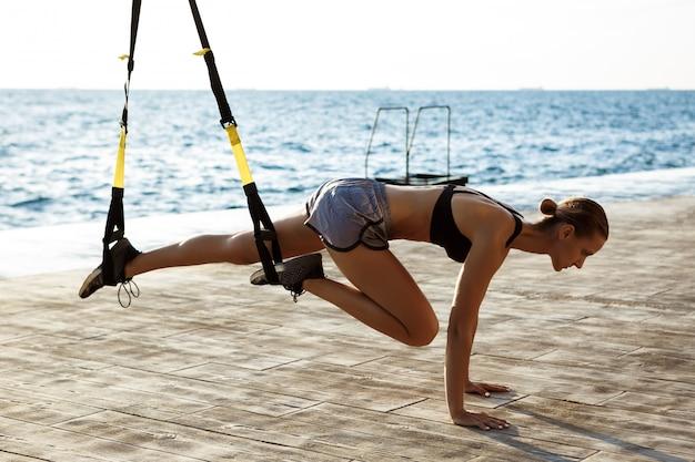 Молодая спортивная тренировка женщины с trx около моря в утре.