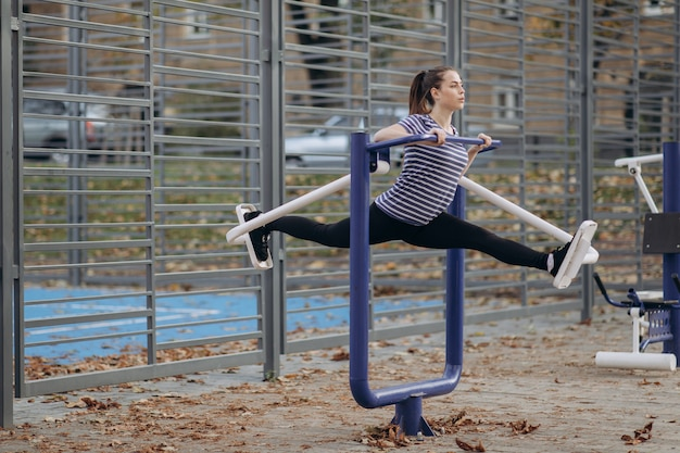 Young sportive woman do walking exercises at outdoor gym