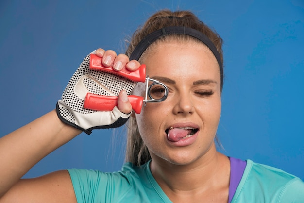 Young sportive woman with a hand stretching gum looking through it.
