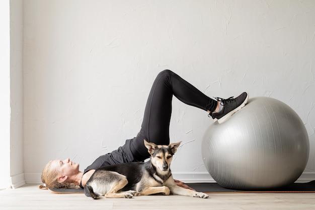 집에서 피트니스 공을 가지고 운동하는 젊은 낚시를 좋아하는 여성