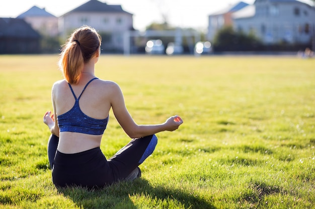 Young sportive woman in yoga position meditates in field at sunrise.