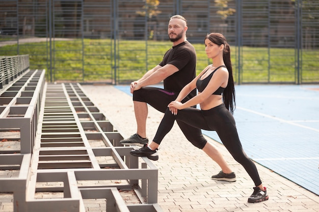 Young sportives at stadium legs exercise Free Photo
