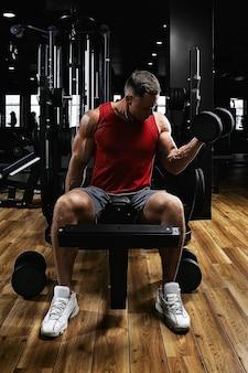 ジムの若いスポーツ選手のフィットネスモデルは、ダンベルで上腕二頭筋を振る。スポーツのモチベーション、ローキー、ハイコントラスト。健康的なライフスタイル、生活の動き、コピースペースの概念。
