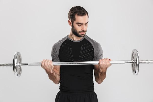 若いスポーツフィットネス男、バーベルでエクササイズをします。