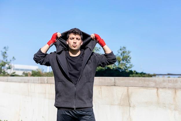 야외 공원에서 젊은 스포츠 피트 니스 남자는 권투 연습을합니다.