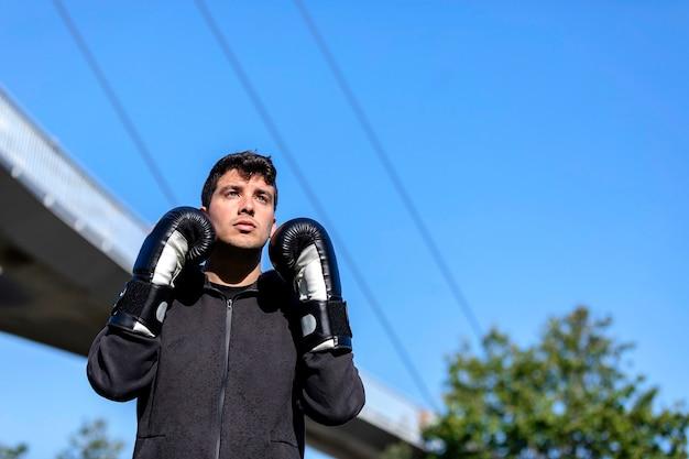 Молодой спортивный фитнес-человек на открытом воздухе в парке делает упражнения по боксу.