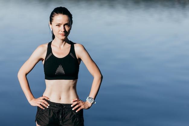 若いスポーツフィットネス女性はイヤホンで音楽を屋外で聴くビーチで残りがあります。