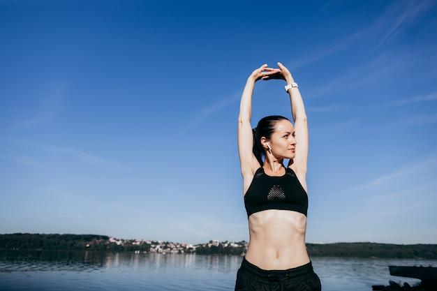 若いスポーツフィットネス女性はイヤホンで音楽を屋外で聴くビーチでストレッチ体操を行います。
