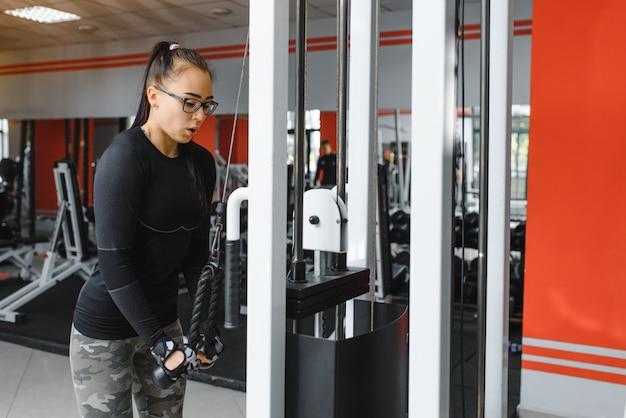 若いスポーツの女の子は、フィットネス、ライフスタイル、スポーツ、健康的な食事に従事し、ジムの女の子は運動をします