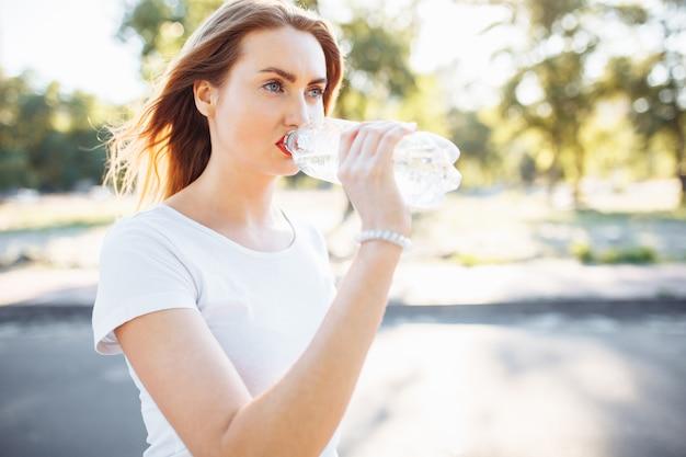 若いスポーツ少女、ハードトレーニングの後、ボトルから水を飲む。