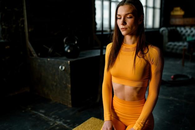 노란색 스포츠 유니폼에 젊은 스포츠 소녀 운동에 대 한 준비. 현대적인 로프트 스타일의 체육관.