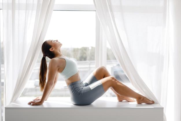 운동 휴식 후 집에서 운동복에 젊은 스포츠 소녀.
