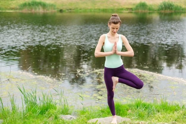 A young sports girl practices yoga on a green lawn by the river