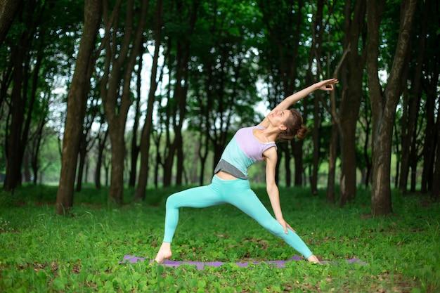 Молодая спортивная девушка занимается йогой в позе асаны йоги в зеленом летнем лесу