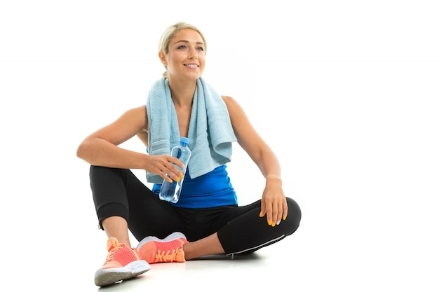 A young sports girl with blonde hair in a black sports axe, black leggings and bright sneakers with a towel around her neck and a bottle of water tired after training.