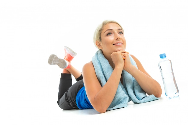 A young sports girl with blonde hair in a black sports top, black leggings and bright sneakers with a towel around her neck and a bottle of water lies.