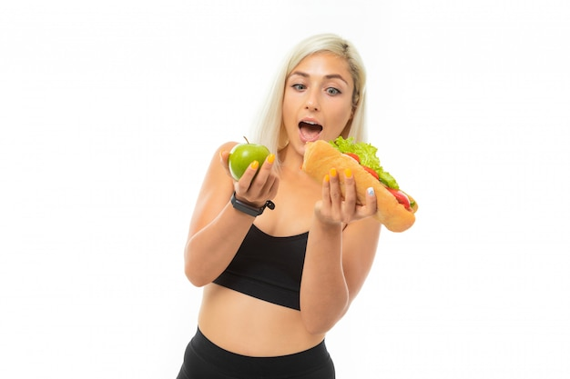 A young sports girl with blonde hair in a black sports top and black leggings holds a green apple and sandwich.