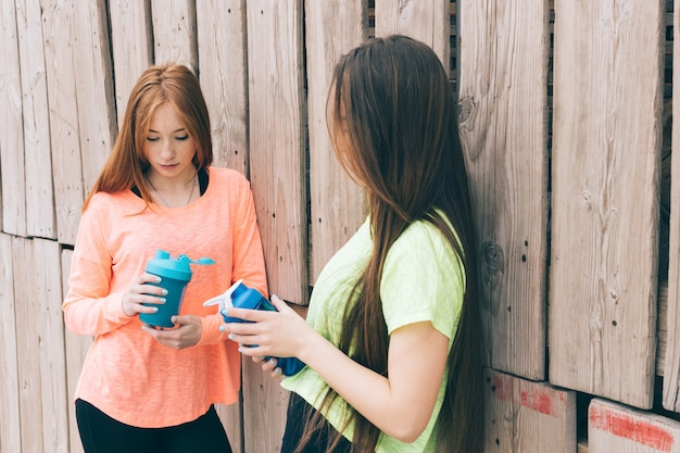 에너지 음료 한 병을 들고 어린 스포츠 소녀