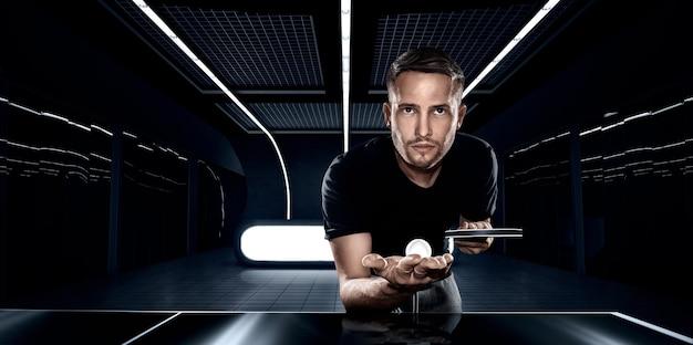 暗い未来的な部屋のクローズアップでピンポンをしている黒いtシャツの若いスポーツ男