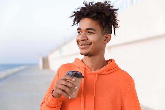 コーヒーを持って飲んでビーチで屋外の若いスポーツ男