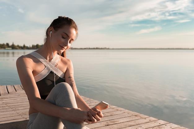 イヤホンで音楽を聴くビーチで若いスポーツ女性。