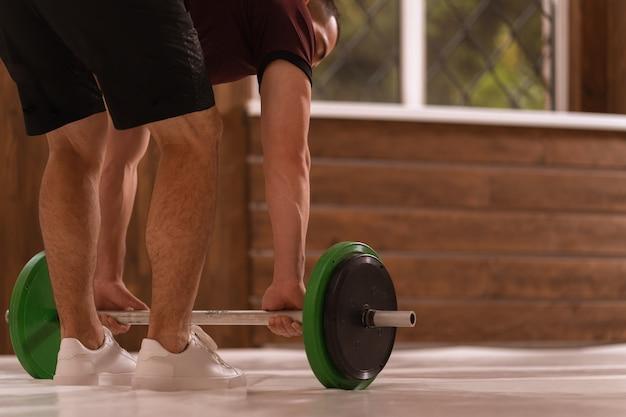 Молодой спортивный человек наклонился, взяв оборудование для силовых тренировок дома