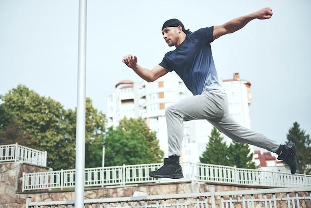 市内のパルクールを行う若いスポーツ男。