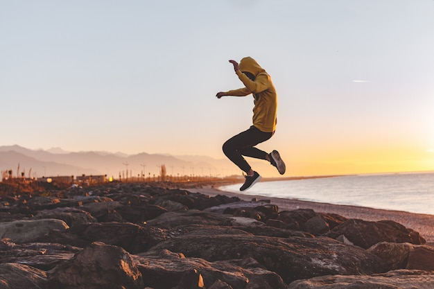 Young sports man in the hood making a jump on the rocks on sea and mountains background at sunset