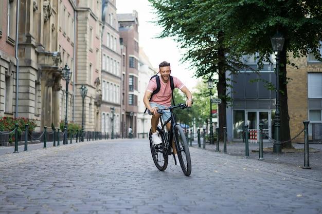 Молодой спортивный человек на велосипеде в европейском городе. спорт в городских условиях.