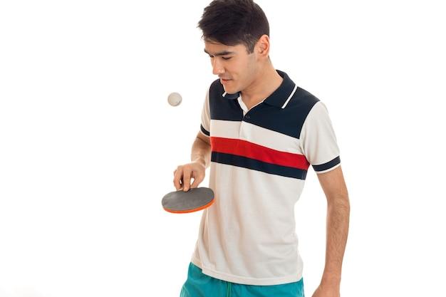白い背景で隔離のピンポンを練習している若いスポーツ男