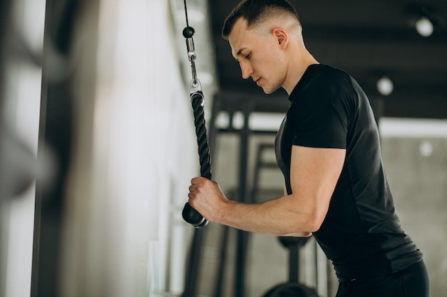 Young sports man training at the gym