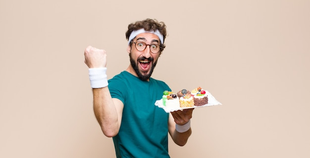 Young sports man with cakes against flat wall