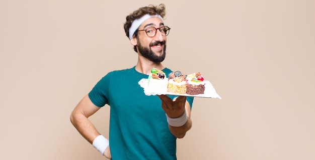 Young sports man with cakes on flat wall