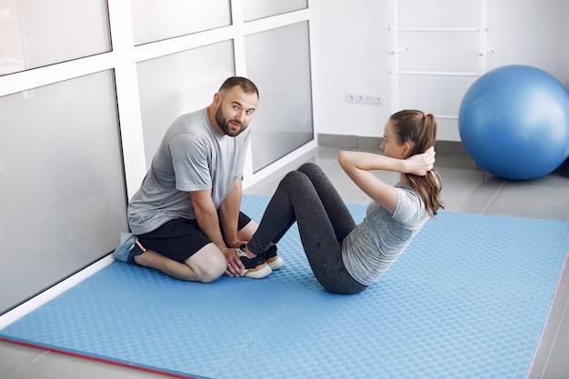 Молодые спортивные люди тренируются в утреннем спортзале
