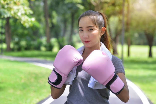 Young sports woman boxing with pink gloves in the park, serious face