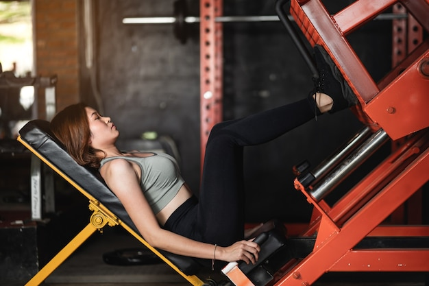 Young sports woman doing fitness exercises for legs muscles in the gym