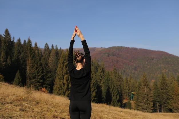 Молодая спортивная женщина делает упражнения йоги на горы и небо осенью