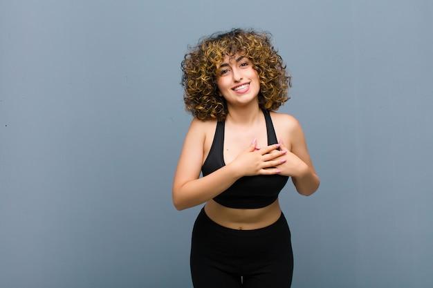 Молодая спортивная женщина чувствует себя романтичной, счастливой и влюбленной, весело улыбается и держится за руки близко к сердцу у серой стены