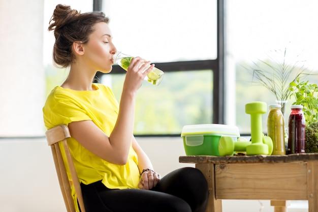 ミントとキュウリと水を飲む黄色のtシャツの若いスポーツ女性。デトックスコンセプト