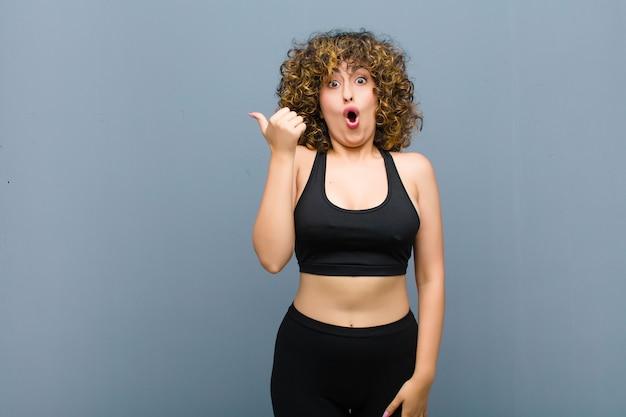 Молодая спортивная женщина выглядит удивленно в недоумении, указывая на объект сбоку и говорит: